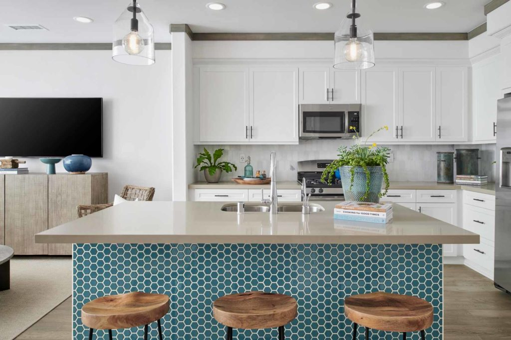 The kitchen island features a splash of ocean blue decorative tile that is as unexpected as it is beautiful.
